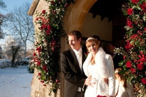 Snowy wedding.bride and groom outside church doorway. Door archway decorated with mixed red flowers and winter foliages