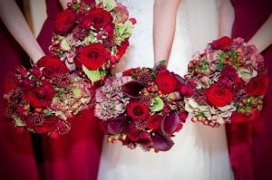 bride and bridesmaids bouquets of mixed red flowers, winter wedding