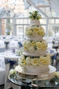 Romantic wedding flowers. 4 tier wedding cake filled with cream roses inbetween