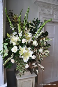 whte plinth arrangement includes large oriental lilies