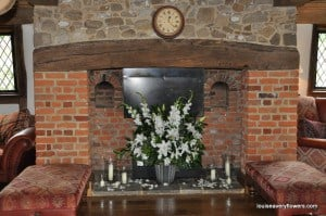 fireplace, white flower arrangement, candles in hurricane lanterns and scattered rose petals