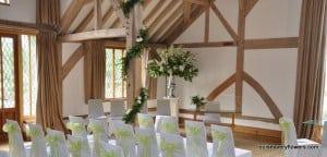 ceremony room, pedestal arrangements and wooden pillard garland