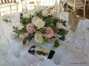 Romantic wedding flowers. Low level round classic table arrangement of cream and pink roses and varigated foliages