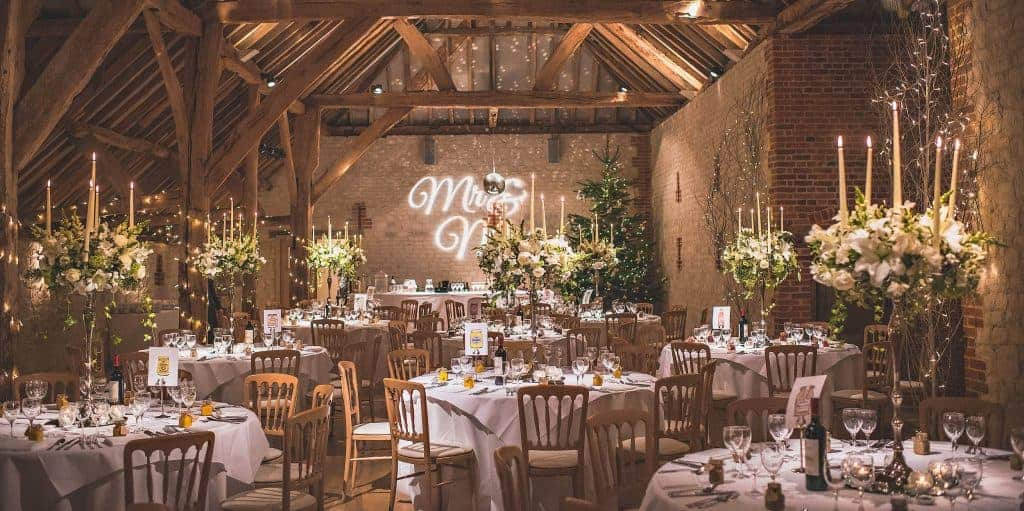 Barn with candelabra table decorations, winter white flowers