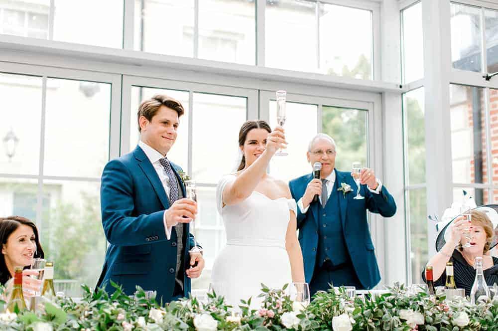 wedding flowersi n Hampshire. Bride and groom toasting glasses