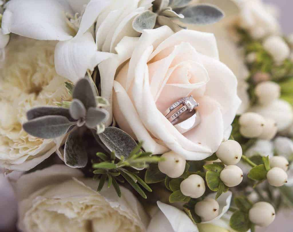 wedding and engagements rings nestled in an open rose