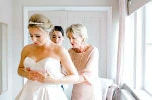 Brides mother helping bride dress