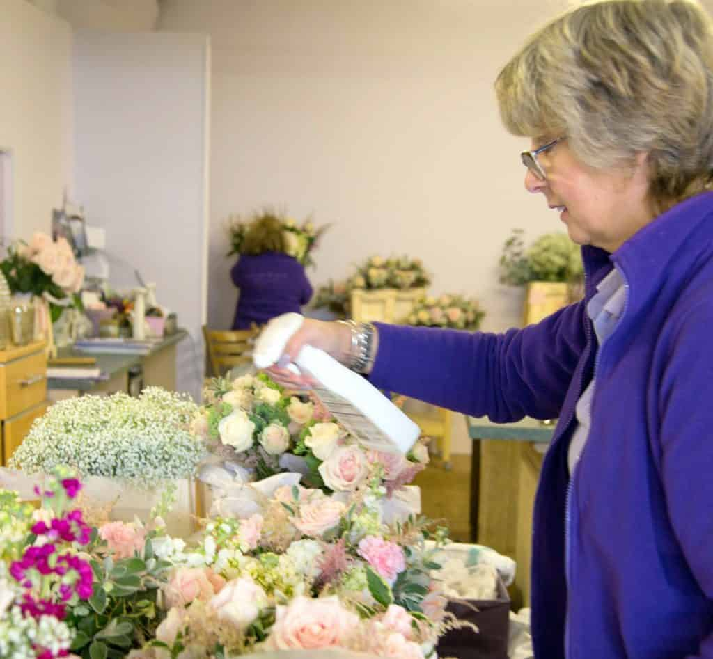 Louise Avery spraying Hampshire wedding flowers with water in the flower studio