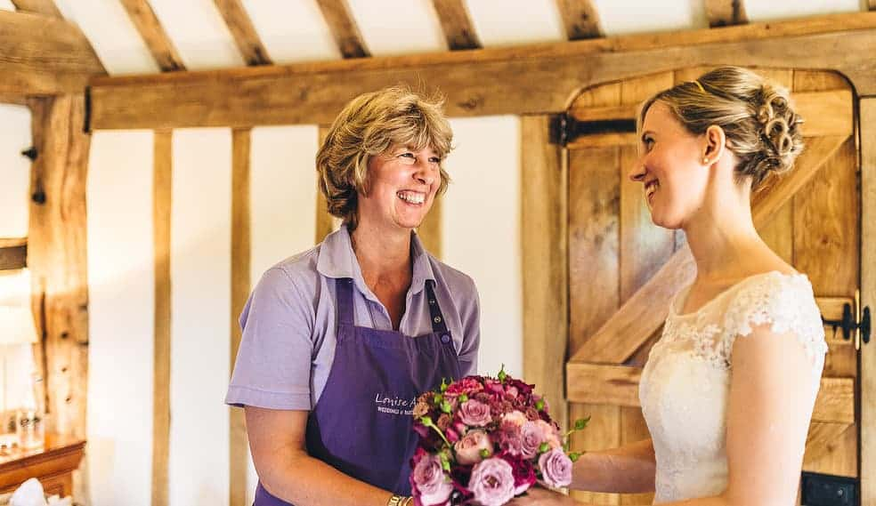 Louise Avery presenting bride with her bouquet Cain Manor Hampshire wedding flowers