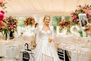 West-Sussex wedding flowers bride with tall table vases