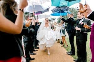 Bride arriving to marquee reception with umbrella guard of honour