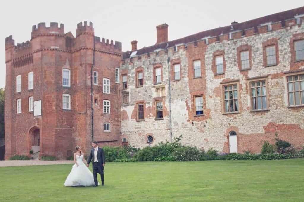 Farnham Castle Weddings. Surrey wedding venue with bride and groom in foreground