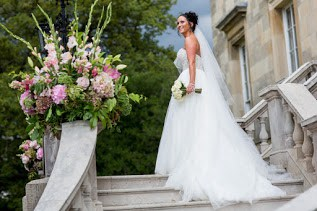 Bride on venue steps holding her bouquet