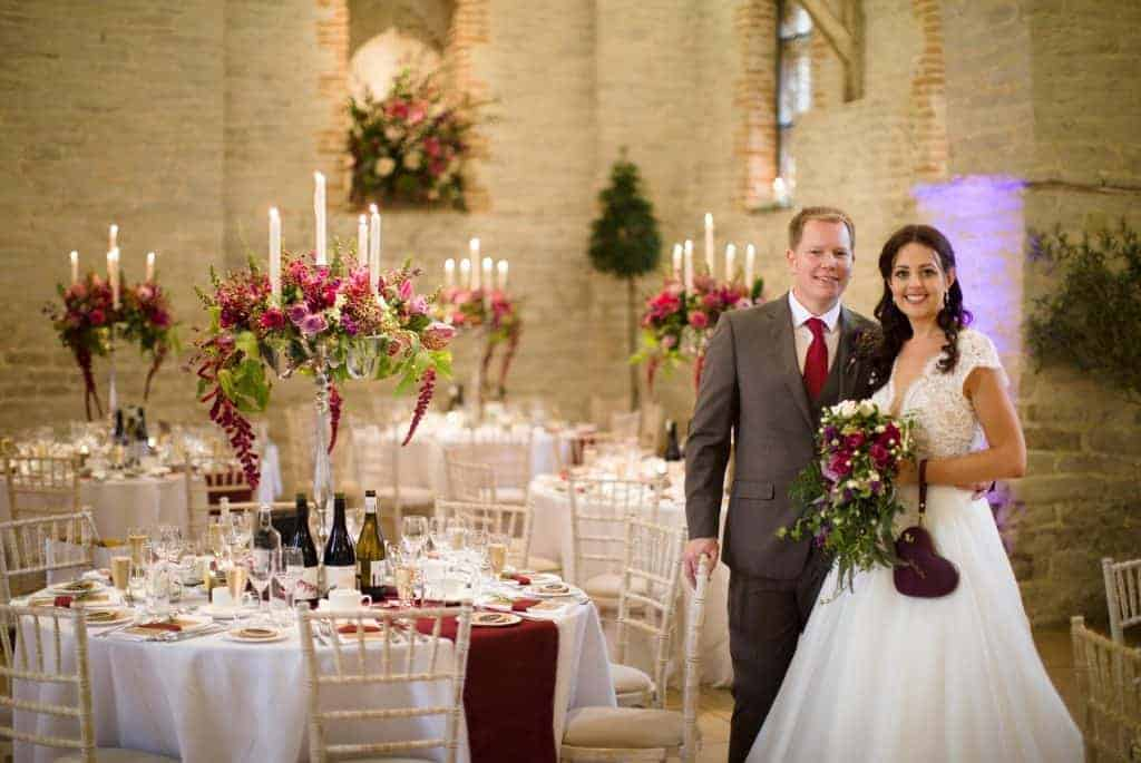 luxury Hampshire wedding. bride and groom in tithe barn, petersfield with floral table candelabra