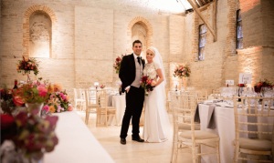 bride and groom at reception surrounded by their autumn wedding flowers